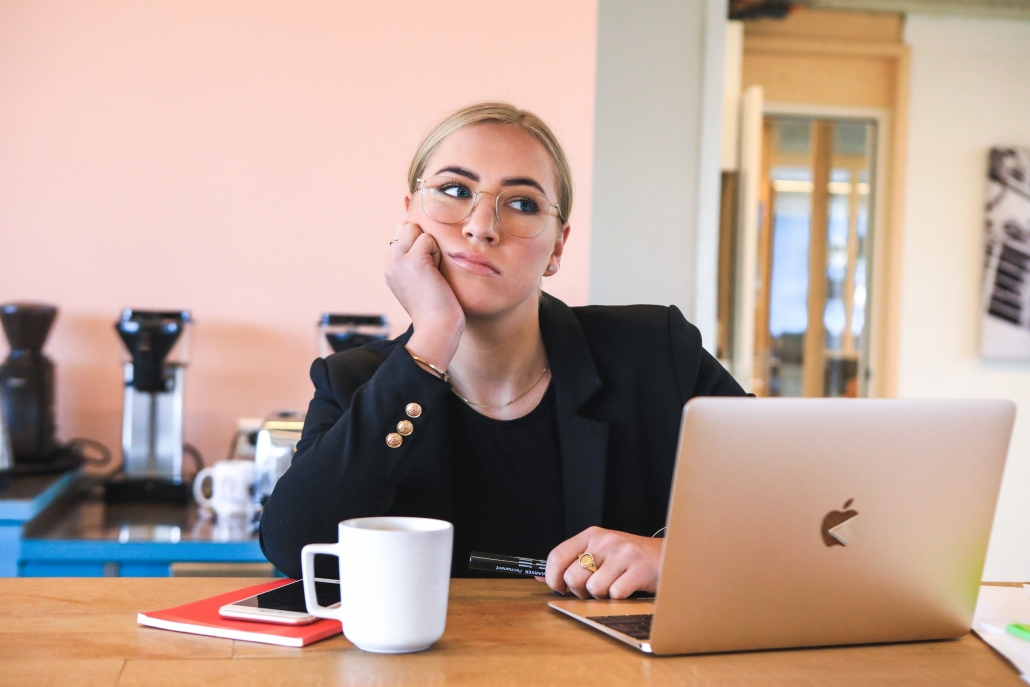 Woman bored and actively experiencing one of these 5 team building mistakes.